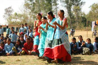 Vier ehemalige Kamalari führen vor dem Beginn eines Theaterstücks einen Tanz auf. Das Stück soll die Schüler auf die Probleme der Kamalari-Mädchen aufmerksam machen. Im Hintergrund sitzen weitere Mädchen und Jungen und sehen zu