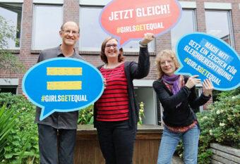 Das Team AG-Koordination: H. Ludwig, M. Sußner, W. Tebbe (v.l.n.r.) mit Sprechblasen zu Girls Get Equal als Schild-Version